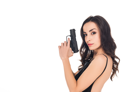 beautiful secret agent in black dress holding gun, isolated on white