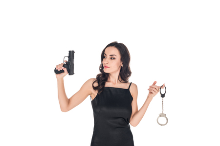 attractive elegant secret agent in black dress holding gun and handcuffs, isolated on white Stock Photo