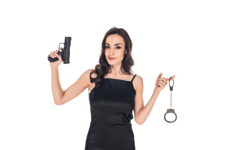attractive smiling secret agent in black dress holding gun and handcuffs, isolated on white