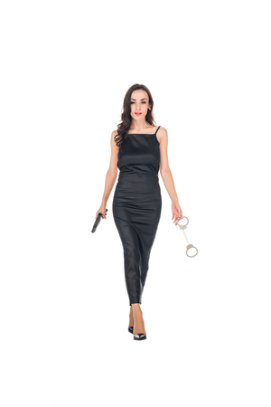elegant female secret agent in black dress holding gun and handcuffs, isolated on white Stock Photo