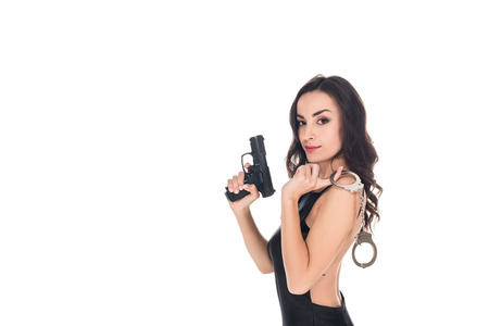 beautiful security agent in black dress holding gun and handcuffs, isolated on white