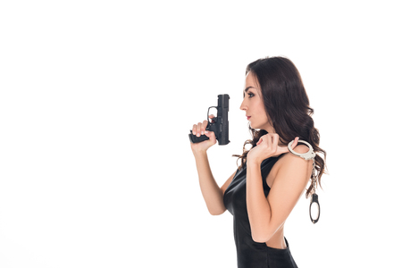 elegant security agent in black dress holding handgun and handcuffs, isolated on white Stock Photo