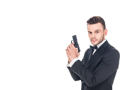 handsome secret agent in black suit holding gun, isolated on white Фото со стока