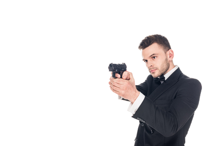 handsome killer in black suit and tie bow aiming with gun, isolated on white
