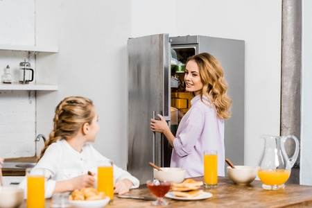 girl sitting at table and looking at mother opening fridge