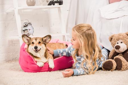 adorable child in pajamas stroking welsh corgi dog at home