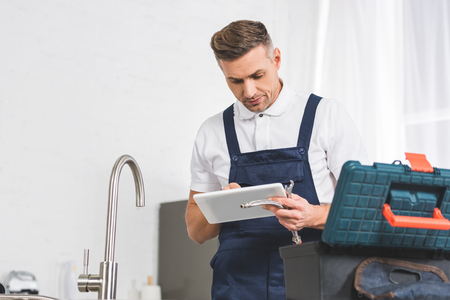 adult repairman using digital tablet and holding tools while repairing faucet at kitchen