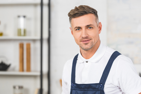 portrait of adult repairman in overall standing at kitchen and looking at camera Reklamní fotografie