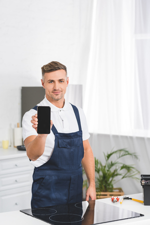 smiling adult repairman showing smartphone with blank screen while standing at kitchen and looking at camera