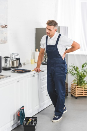 full length shot of thoughtful adult repairman holding pliers while leaning on kitchen counter