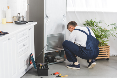adult handyman repairing refrigerator at kitchen with tools on floor 스톡 콘텐츠