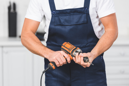 cropped view of repairman holding drill inhands Reklamní fotografie