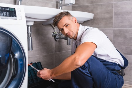 adult repairman sitting on floor and holding repair tool at bathroom and looking at camera