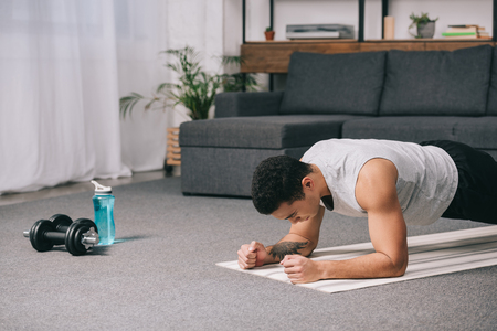 bi-racial man doing plank exercise on  fitness mat in apartment