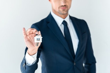 cropped image of businessman holding key from house isolated on white
