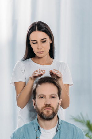calm man looking at camera while receiving reiki treatment from young female healer Фото со стока