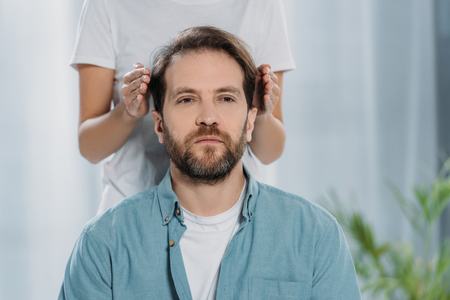 cropped shot of bearded man sitting and receiving reiki treatment on head