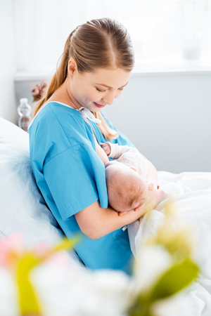 side view of smiling young mother breastfeeding newborn baby on bed in hospital room