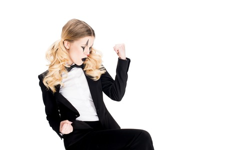 blonde female clown standing in suit and showing muscles isolated on white