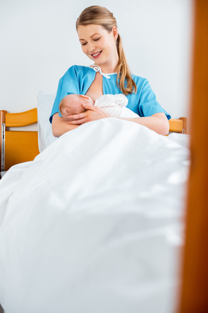 selective focus of beautiful happy young mother breastfeeding newborn baby on bed in hospital room Stock Photo