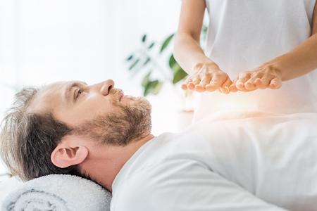 abgeschnittene Aufnahme eines bärtigen Mannes, der während einer Reiki-Behandlung aufschaut