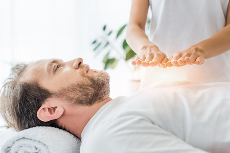 cropped shot of bearded man looking up while receiving reiki treatment