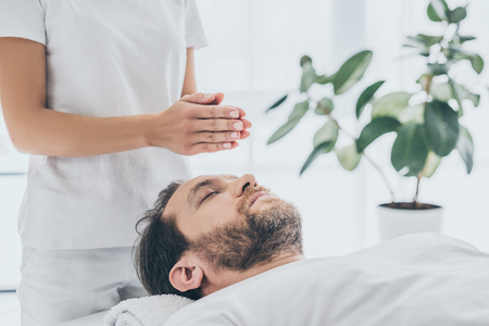 cropped shot of female hands and bearded man receiving reiki treatment