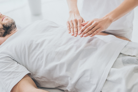 cropped shot of bearded man receiving reiki treatment on stomach Stock Photo