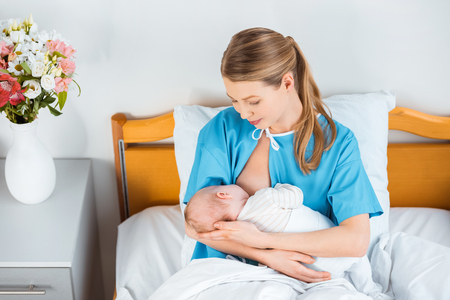 high angle view of happy young mother breastfeeding newborn baby on bed in hospital room