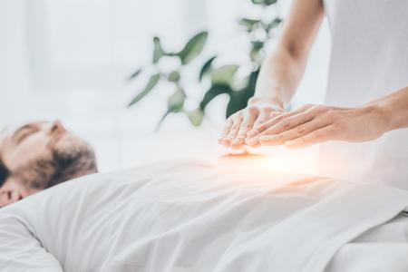7/8-Aufnahme eines Mannes, der eine Reiki-Behandlung am Bauch erhält