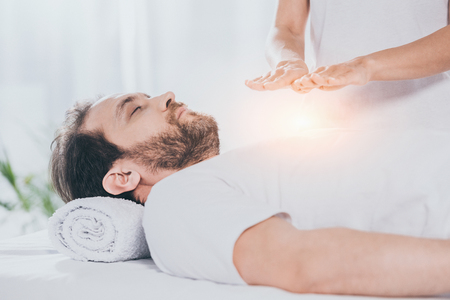 cropped shot of bearded man with closed eyes receiving reiki treatment on chest