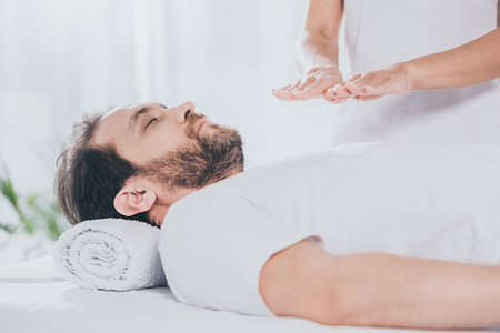 side view of bearded man with closed eyes receiving reiki treatment on chest