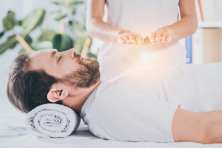 side view of calm bearded man with closed eyes receiving reiki treatment Imagens