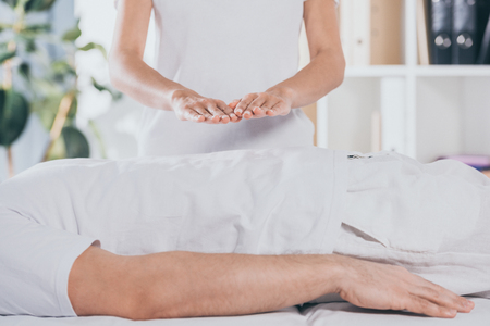 cropped shot of man lying on massage table and receiving reiki treatment Reklamní fotografie