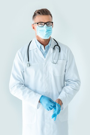 handsome doctor in medical mask wearing medical gloves and looking at camera isolated on white