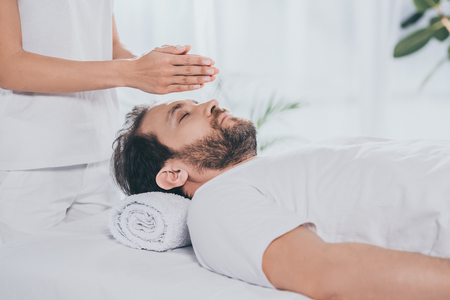 cropped shot of bearded man with closed eyes receiving reiki treatment above head Stock Photo
