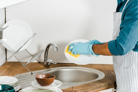 cropped image of mature man washing dishes in kitchen