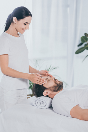 smiling young woman doing reiki treatment session to calm bearded man with closed eyes Stock Photo