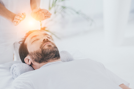 calm bearded man with closed eyes receiving reiki healing session Фото со стока