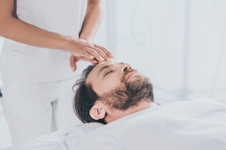 calm bearded man with closed eyes receiving reiki healing therapy on head