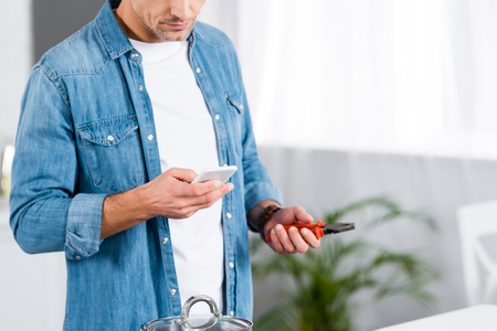 cropped view of man holding smartphone and pliers in hands