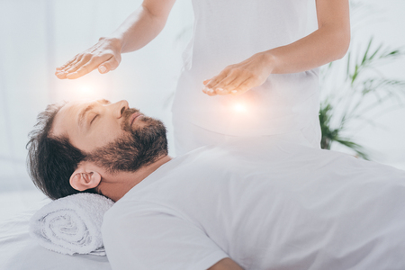 cropped shot of bearded man with closed eyes receiving reiki healing treatment