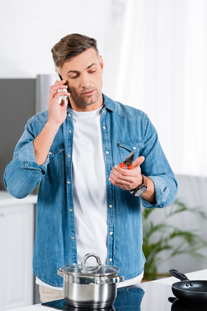 handsome man talking on smartphone and holding pliers in hand while standing in kitchen