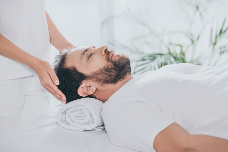 cropped shot of man with closed eyes receiving reiki treatment Standard-Bild
