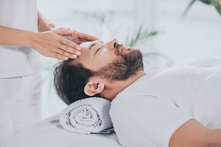 cropped shot of reiki specialist doing healing session to calm bearded man with closed eyes