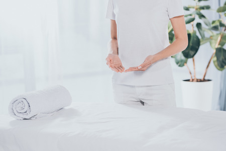 mid section of reiki healer standing near white massage table Stock Photo