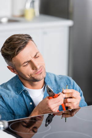 handsome man repairing wires of electric stove