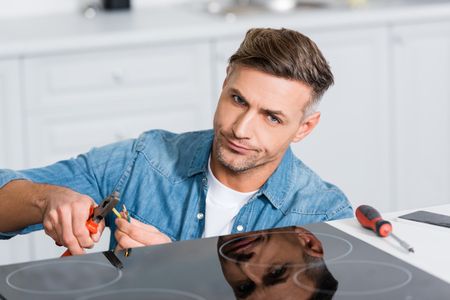 confused man repairing wires of kitchen stove