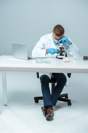 handsome chemist in medical mask and medical gloves looking at microscope isolated on white Banco de Imagens