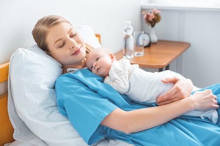 junge Mutter schläft auf Krankenhausbett mit entzückendem Baby auf der Brust liegend lying Standard-Bild